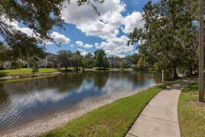 Sidewalk next to lake and trees